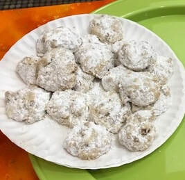 Paper plate of crumbly nut round cookies with confectioner's sugar sifted on top
