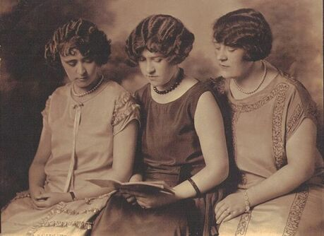 Three young women of the 1920s reading a book